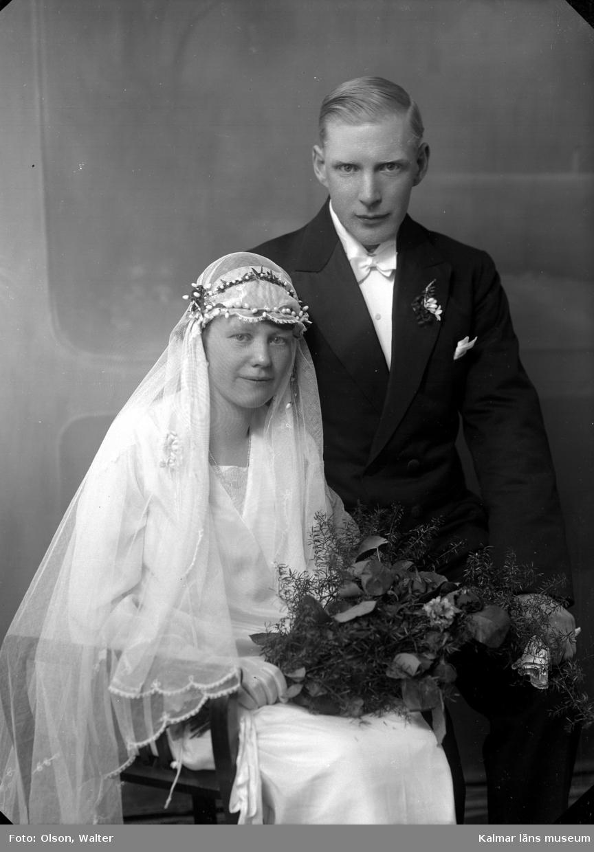 Bröllopsbild i ateljé, kvinnan har slöja och håller i en blombukett. Mannen har frack. Enligt Walter Olsons journal är bilden beställd av Henning Gustavsson ifrån Södra vägen 37 A i Kalmar.