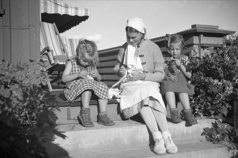 Guri og Siri sitter ute og strikker sammen med barnepleier på terrasse. Fotografert 1935. (Foto/Photo)