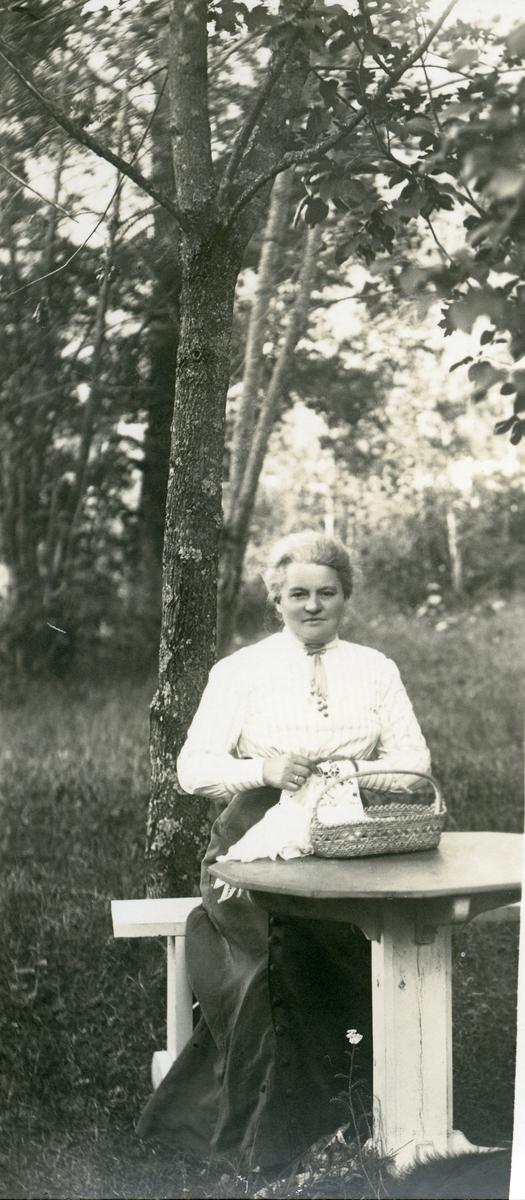 En kvinne sitter ved et bord i en hage. Hun holder sysaker i hendene.
