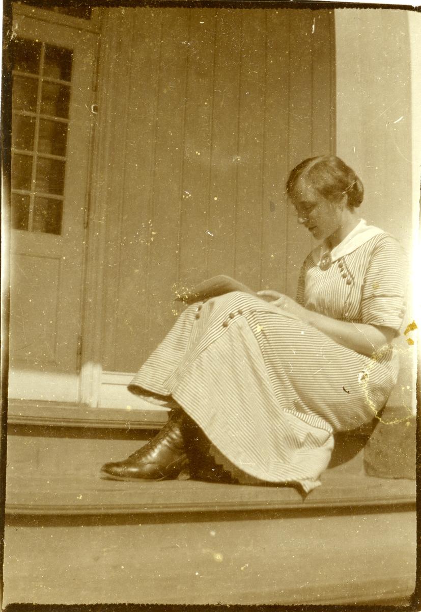 En kvinne sitter på en trapp og leser. Kvinnen er iført kjole og støvletter.