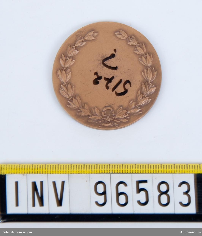 Medalj i brons för Skånska kavalleriregementet. Stans 20963, härdad 1949-09-08. Medalj, åtsida med strålformig stjärna med 2 regementsfanor, den ena med skånska gripen samt inskr. LANDSKRONA 1677, PULTUSK 1703, POSEN 1704, FRAUSTADT 1706, med tre kronor krönt av kungl. krona som fanspets. Den andra med svärd och kunglig krona samt 4-armat kors jämte inskr. BORNHÖFT D. 7 DEC. 1813 samt med kronor i hörnen med Gustaf V:s namnchiffer som fanspets, inom omskrift KUNGL. SKÅNSKA KAVALLERIREGEMENTET. Modell: Åke Hammarberg.