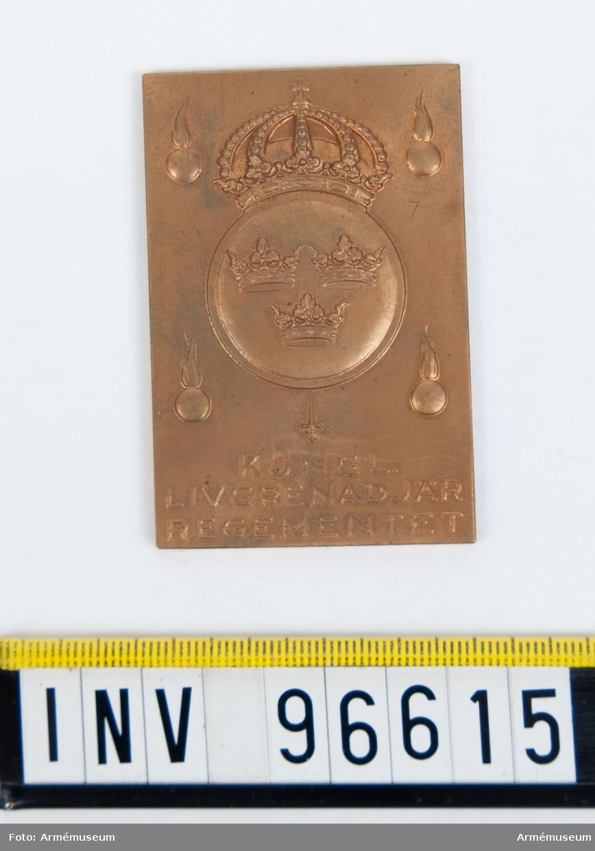 Plakett i brons för Livgrenadjärregementet. Stans nr 7743 härdad 1936-05-09. Plakett upptagande tre kronor på runt fält med kungl. krona, omgivet av fyra granater samt därnedanför ett svärd, med inskr. KUNGL. LIVGRENADJÄRREGEMENTET.
