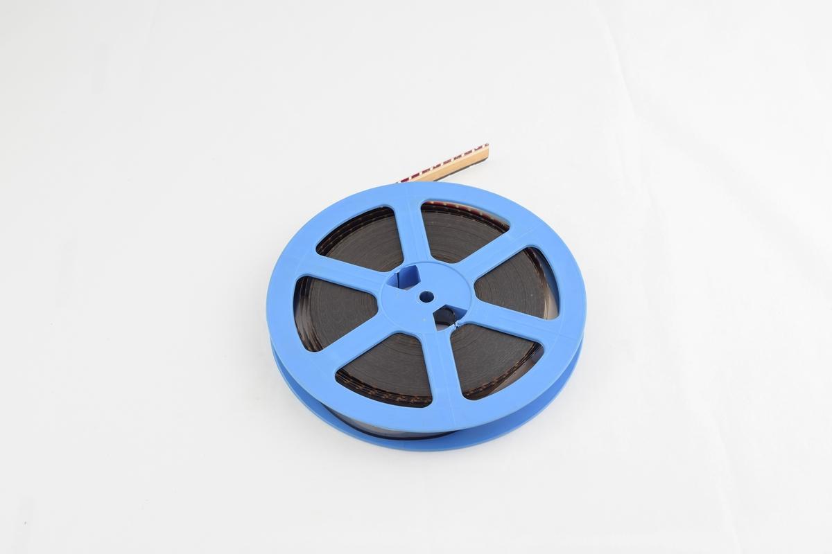Filmrull i eske. Film på metallspole. Firkantet papir etui åpnes langs en av sidekantene, festes med lærstropper med metallspenne.
