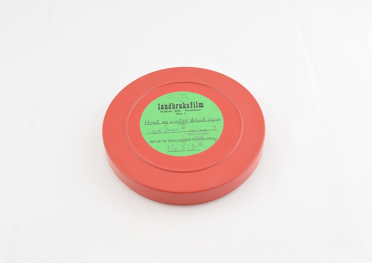 Filmrull i eske. Film på rød plastikkspole. Rødt rundt etui med rund grønn etikett.