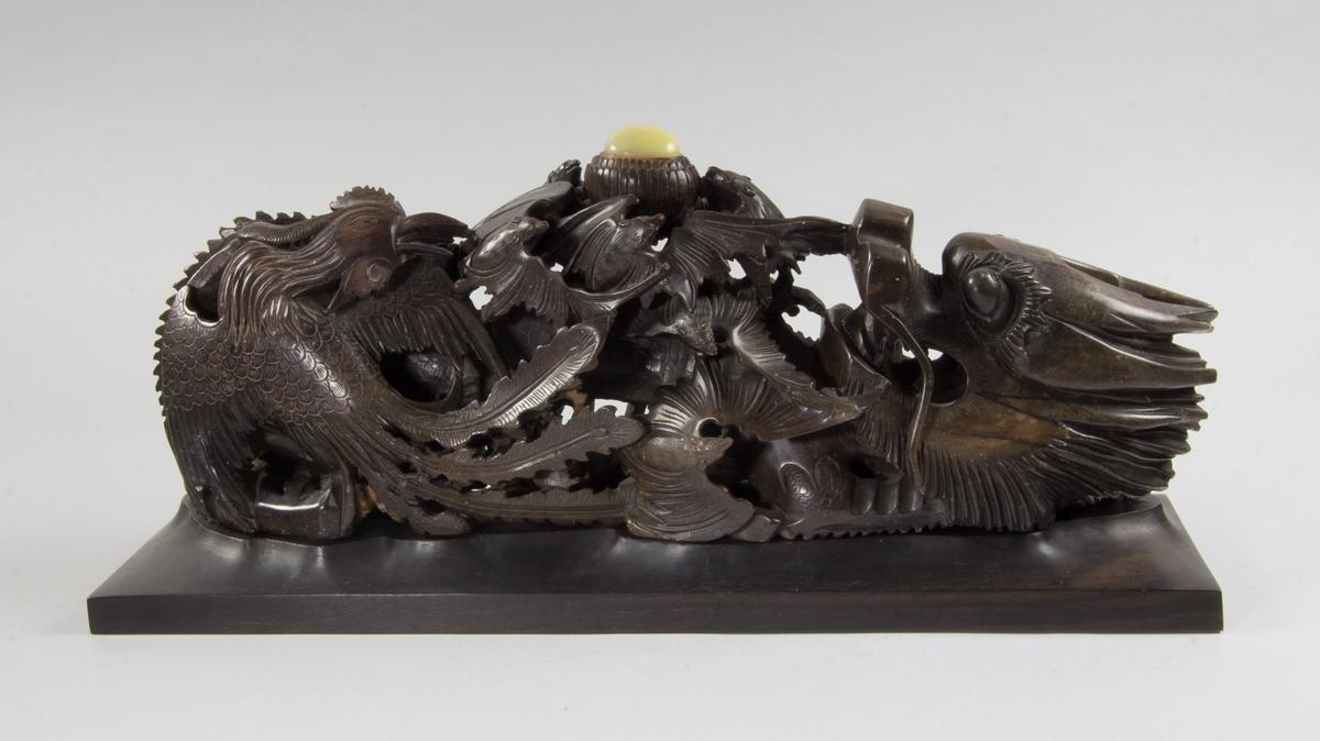 Prydnadsföremål, avlångt, av mörk sten, späcksten, skulpterat och genombrutet föreställande drake, fågel Fenix och fladdermöss. Krönt av gulaktig oval halvädelsten. Monterad på rektangulär svart sockel av trä, troligen ebenholts.