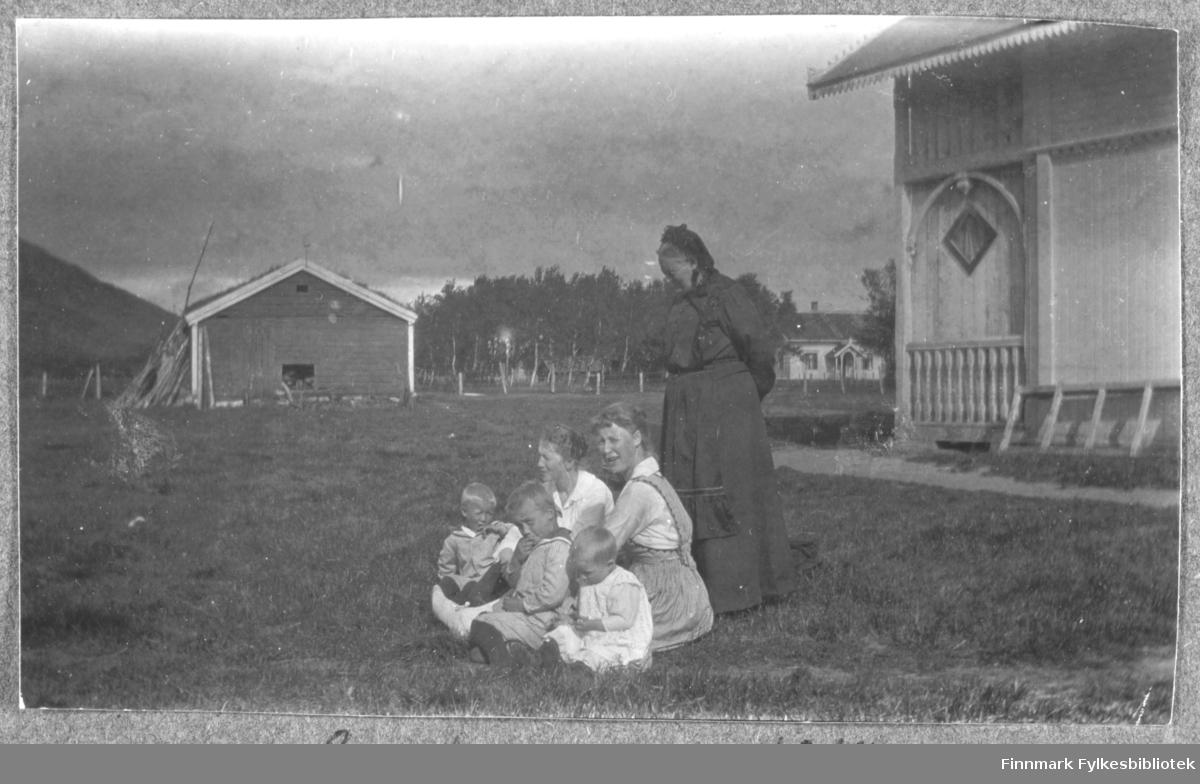 Grande. Sommeren 1918. Kvinner og barn sittende i gresset, i solen. En trebygning til høyre i bildet, et hus i bakgrunnen til høyre og et uthus eller låve til venstre. Barna har på seg matrosdress eller hvite forklær. Kvinnene som sitter har hvite bluser og den ene har forkle. Den eldre kvinnen som står bak gruppen har sorte klær og et hodeplagg på hodet. Hun har sort forkle utenpå skjørt og bluse.