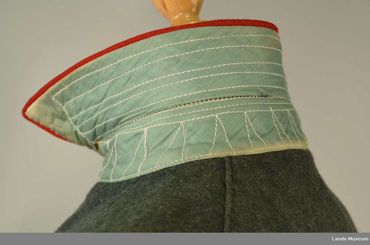 Jakke: Enkelt kneppet-to stikklommer, to innerlommer. Spensel bak. Blårutete for.  Bukse: Gråhvit for i linning og lommer. Merket VI bak. Stempel i linning. Buksebens er sydd ut med ein linning.