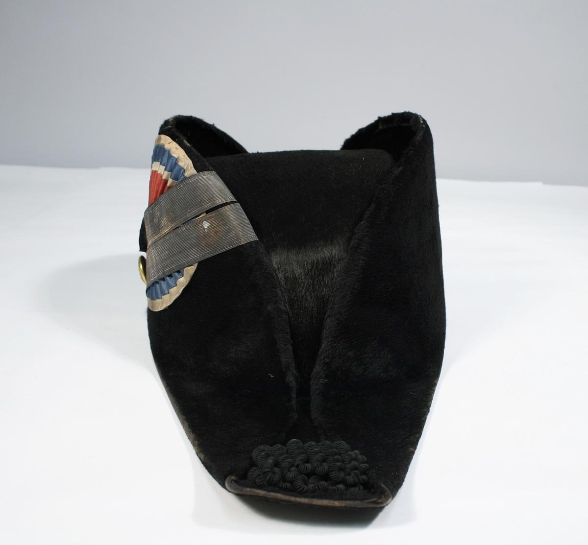 Flosset stoff, snutene forsynt med possement prydelser i sort. På høyre side kokarde, og bånd festet med knapp, riksløven av 1844.  Hatten har original hakerem.