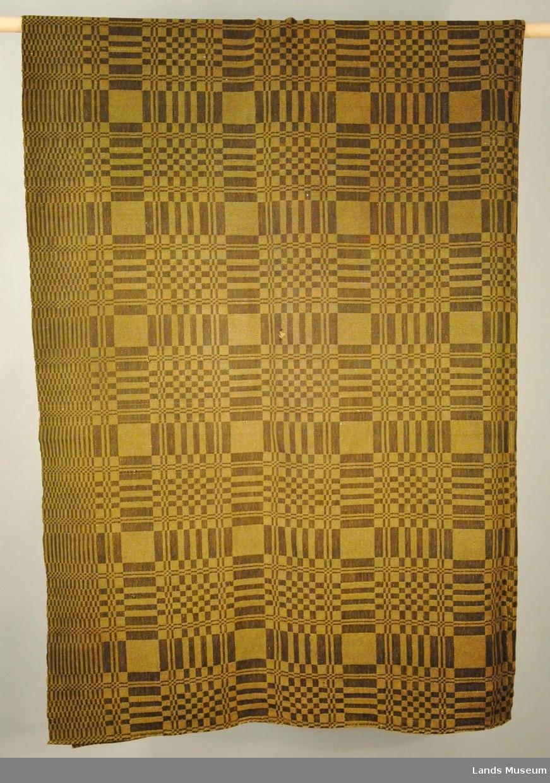 Vevd i dreielsvev. Sort bomullstråd i renning, gulgrønn ulltråd i vefting. Teppet er samansydd på midten.