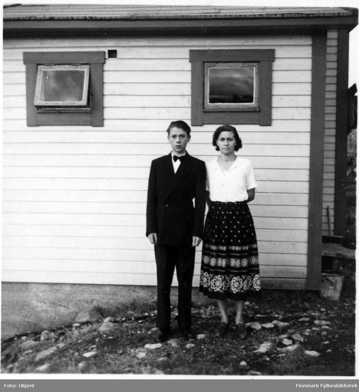 Odd Martinsen som komfirmant. Ved siden av står hans mor Astrid Martinsen. Odd er kledd i dress: jakke, bukser og sløyfe rundt halsen. Astrid har på seg kjorte, skjørt og sko. De står utenfor et hus med vindu. På høyre siden av bildet kan man se et spann og en kost.