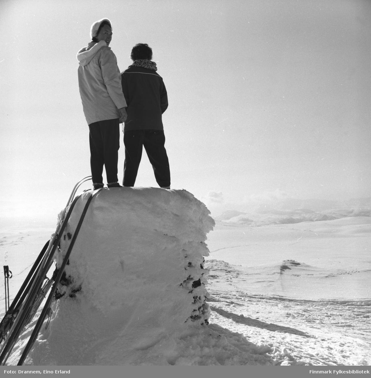 To damer står på et snødekt sylinder-formet byggverk. Jenny Drannem til høyre på bildet, den andre er ukjent.