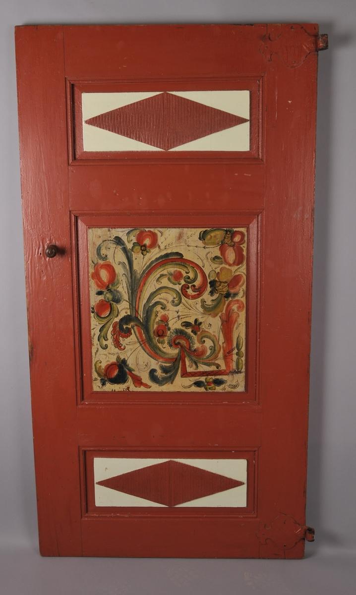 Dør med tre fyllingar, dekorert i ei fylling på eine sida og i tre på andre sida. Sekundær maling på rammtre.