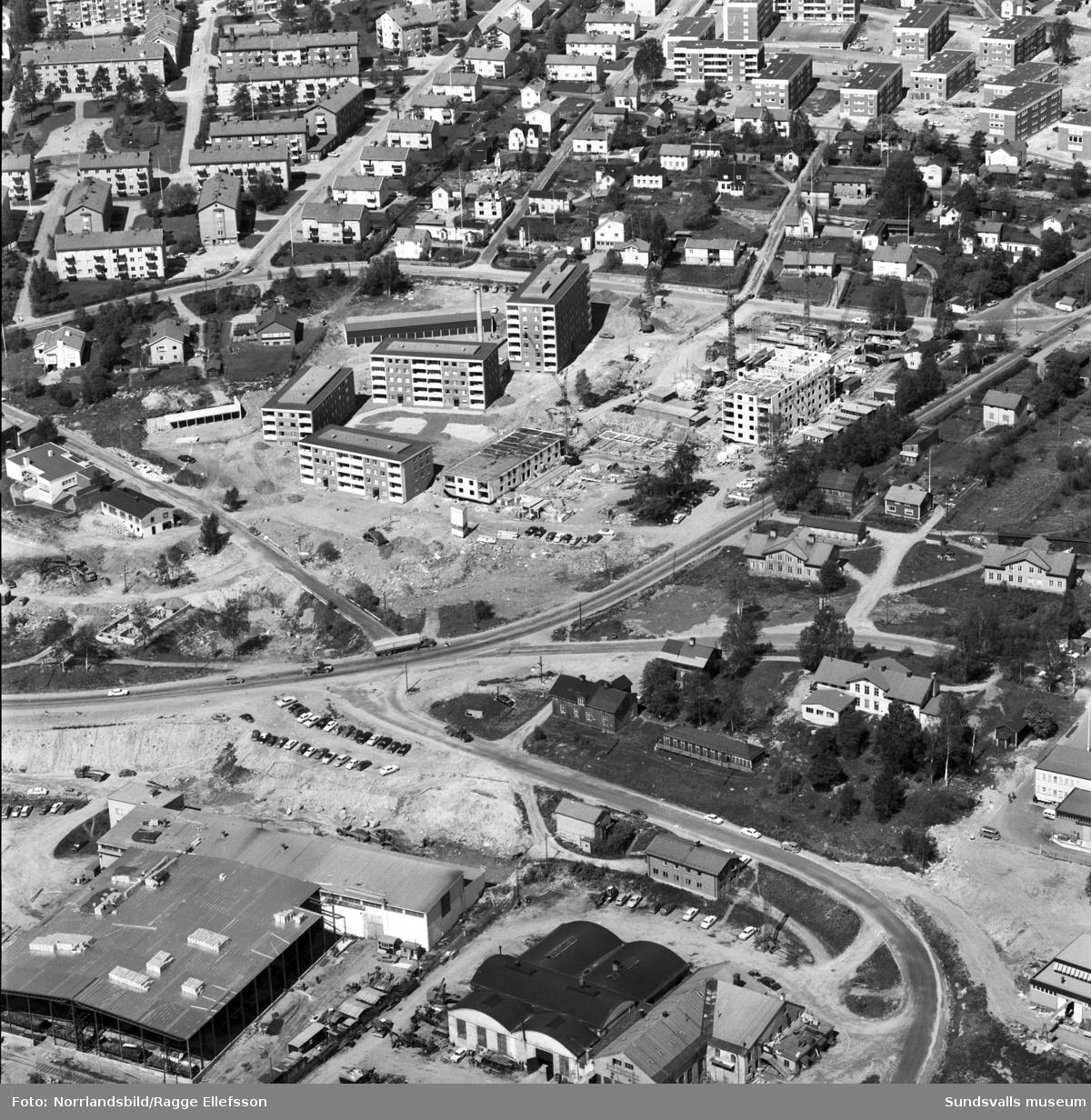 Flygfoto över västra Skönsberg och Heffners med bygget av flerfamiljshusen vid Trafikgatan, Basgränd, Skönsbergsvägen. I överkanten syns även de nya husen vid Riddargatan och däremellan finns gammal villabebyggelse ännu kvar.