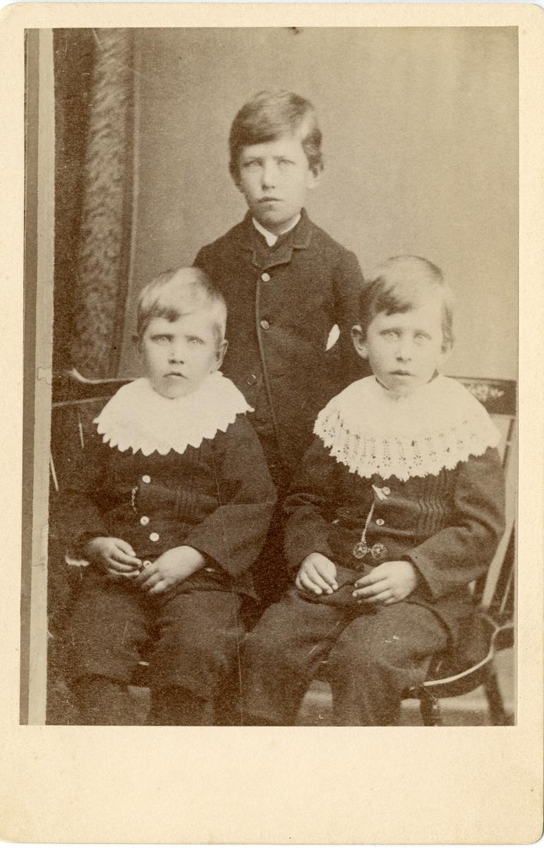 Portrett av tre gutter. Alle er kledd i mørke knebukser og jakker. De to minste har store hvite heklete krager.