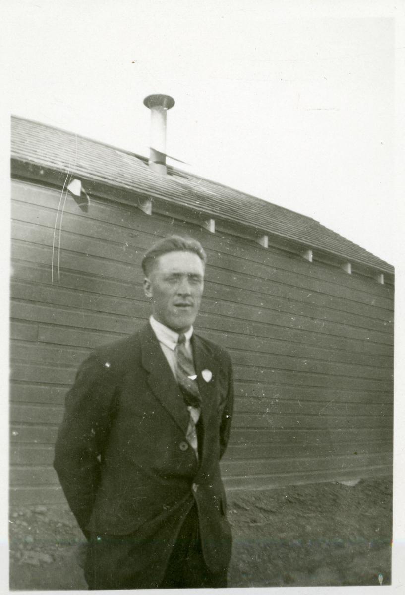 Portrett av en mann foran en husvegg. Mannen er iført dress og slips.