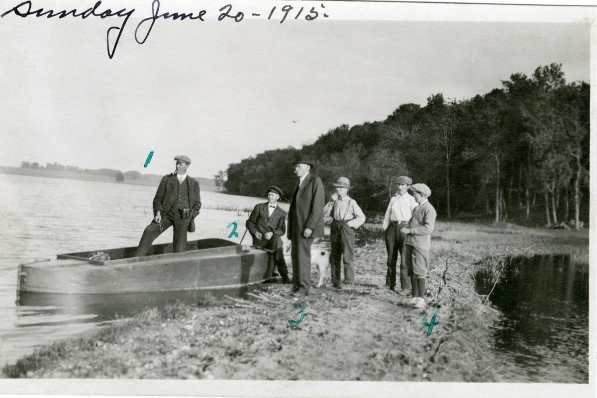 6 karer står ved siden av en slags robår ved bredden av en innsjø i Amerika. De er alle familien Knatvold. Fra venstrer står Haldor, Burt og Edward. Lengst til høyre står Haldor sin sønn.