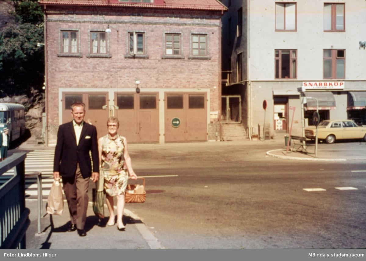 En kvinna och en man vid Gamla Torget i Mölndal, 1970-tal. I bakgrunden ses huset Kvarnbygatan 41, tidigare brandstation och garage för polisbilar, numera Mölndals målarskola. Till höger ses liten del av huset Kvarnbygatan 43, tidigare Mölndals stadshus, sedermera musikskola. Vy från Forsebron.  För mer information om bilden se under tilläggsinformation.