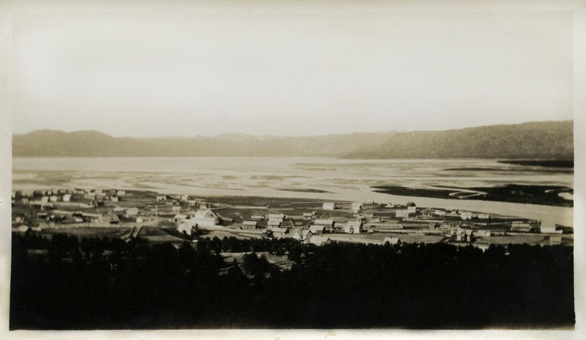 Fotografi av Alta. Man kan se flere hus nært havet, og fjell i bakgrunnen.
