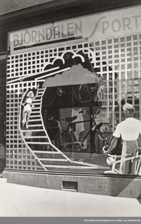 Ole M. Engelsens fotografier fra okkupasjonsårene i Oslo. Slik ble vindusrutene sikret for å hindre at glasset skulle splintres ved flyangrep. Lemmene og sanden skulle gjøre tilfluktsrommene i kjelleren tryggere..Bjørndalen Sport i Markveien 58. .Mai 1940.