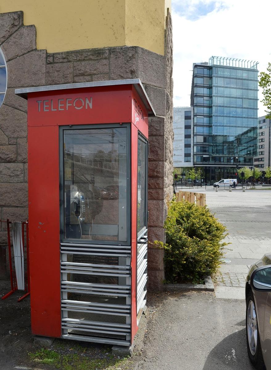 Denne telefonkiosken står i Drammensveien 157 ved Skøyen togstasjon, og er en av de 100 verna telefonkioskene rundt om i Norge. Jernbanestasjoner var typiske steder der Telenor plasserte slike offentlige telefonkiosker. Ofte stod det flere ved siden av hverandre. De røde telefonkioskene ble laget av hovedverkstedet til Telenor (Telegrafverket, Televerket) Målene er så å si uforandret.  Vi har dessverre ikke hatt kapasitet til å gjøre grundige mål av hver enkelt kiosk som er vernet.  Blant annet er vekten og høyden på døra endret fra tegningene til hovedverkstedet fra 1933. Målene fra 1933 var: Høyde 2500 mm + sokkel på ca 70 mm Grunnflate 1000x1000 mm. Vekt 850 kg. Mange av oss har minner knyttet til den lille røde bygningen. Historien om telefonkiosken er på mange måter historien om oss.  Derfor ble 100 av de røde telefonkioskene rundt om i landet vernet i 1997. Dette er en av dem.