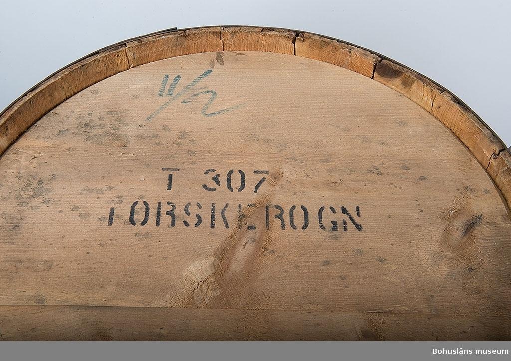 """Laggad trätunna med fyra järnband, två med ås. Två lösa lock/bottnar. Enligt uppgift norska. Två stycken likadana. På det ena locket/bottnen texten: """"T307 torskerogn"""" [torskrom] samt 11/2."""