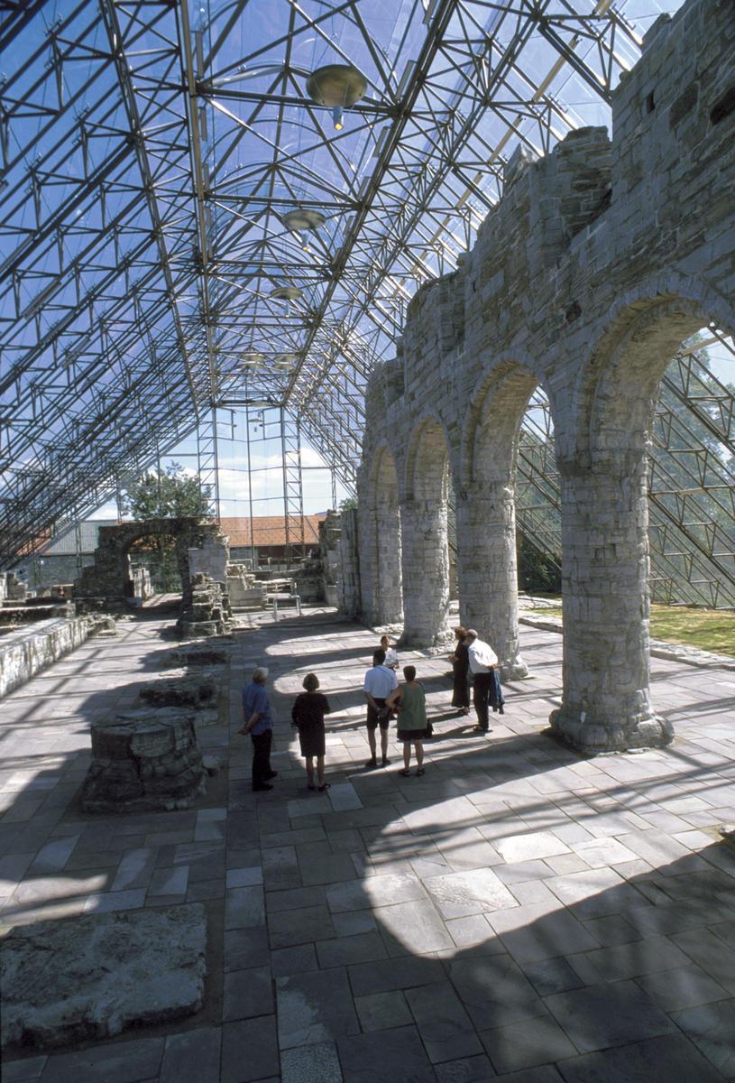 Domkirkeruinen under vernebygg i stål og glass, noen besøkende går oppover i midtskipet.