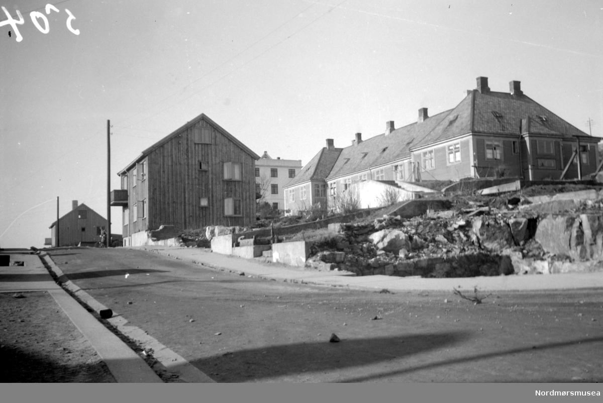 """Bilde fra Gomagta med Freiveien til høyre. Branntomten til høyre, med kommunens leiegård populært kalt """"Arken"""", som er bygd ca 1918. I midten ser vi nyreiste hus i Gomagata. Bildet er fotografert fra øst, og datert Mai 1943. Nordmøre Museums fotosamling"""