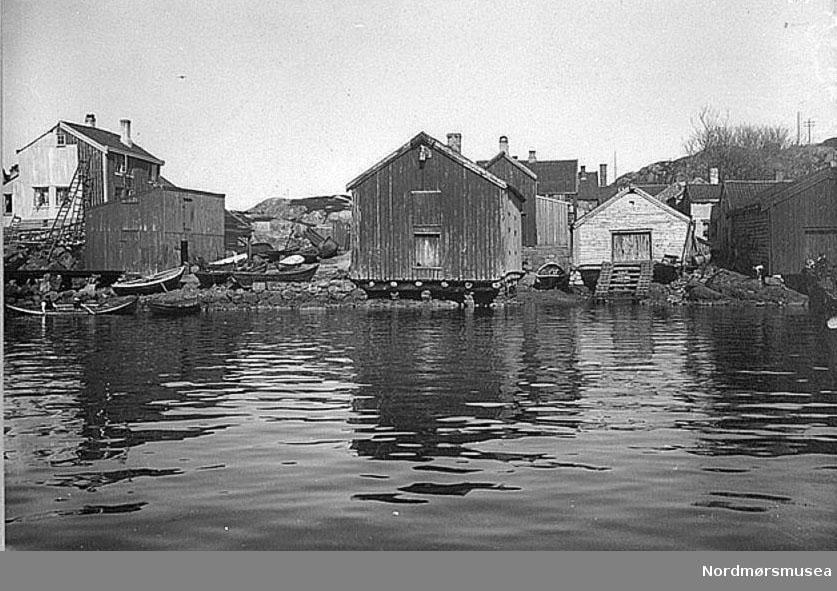 """79 Parti fra Hønebukta, Indlandet. Fot. for D. K. L. i 1909. Fra høyre til venstre sees i bildets forgrunn følgende hus: Lengst til høyre et stykke av et nøst tilhørende bryggearbeiderne Bjerkeseth og Aafløy, nøst tilhørende los A. Kleve, nøst tilhørende los Thomas Lervig, bak dette litt til høyre nøst tilhørende fru Lund, og bak samme nøst litt til venstre, nøst tilhører Grønseth. Lenger til høyre fisker Tranes nøst. Så følger et klosett med pulttak og delvis hvilende på stolper som står ute i sjøen. Klosettet tilhører ovennevnte fisker Trane, hvis temmelig store vånegård sees like bakenfor. Dernest tilhørende firmaet J. P. Clausen ( Gram Parelius) i dette sees flere barn. Så følger med gavlen rett frem nøst tilhørende fiskehandler Anton Myrseth, dernest J. Thoresens bøkkerverksted, som tidligere var brakke tillhørende byens gamle sykehus på Innlandet.Så følger en kai tilhørende nevnte J. Thoresen, og som kalles""""Toresenkaia"""". På denne sees flere båter liggende. Dernest kommer et materialhus for bøkkerverkstedet; dette har pulttak. Denne kaien fortsetter så av en delvis ny kai, oppført på pillar. Bak Grønseths nøst på bildets høyre parti står også et nøst tilhørende fisker Rødal; men dette kan ikke sees på bildet. Nøstene her i Hønebugta blir av innbyggerne her kalt etter deres eiere for """"Grønsethnaustet"""", """"Rødalsnaustet"""", """"Lervignaustet"""" osv. Naustene er til dels bordkledde; et av dem har tak bekledd med bølgeblikk, 2 har gresstorvtak, nemlig """"Clausennaustet"""" og """"Klevenaustet"""". Alle disse nøst brukes ennu som """"båtnaust"""" og til oppbevaring av fiskeredskaper, i et, nemlig fru Lunds nøst brukes som båtbyggeri, som drives av brødrene Johan og Olai Olsen. Nøstene er til dels bortleide til fiskere som bor på Innlandet. """"Grønsetnaustet"""" og """"Klevenaustet"""" er således bortleide til fiskere. Således blilr det flere fiskere som her i nøstene har sine fiskeredskaper. Av eierne eller leierne av nøstene bor etter mundtlig meddelelse av overnevnte fisker, Rødahl, Anton Myrseth og """