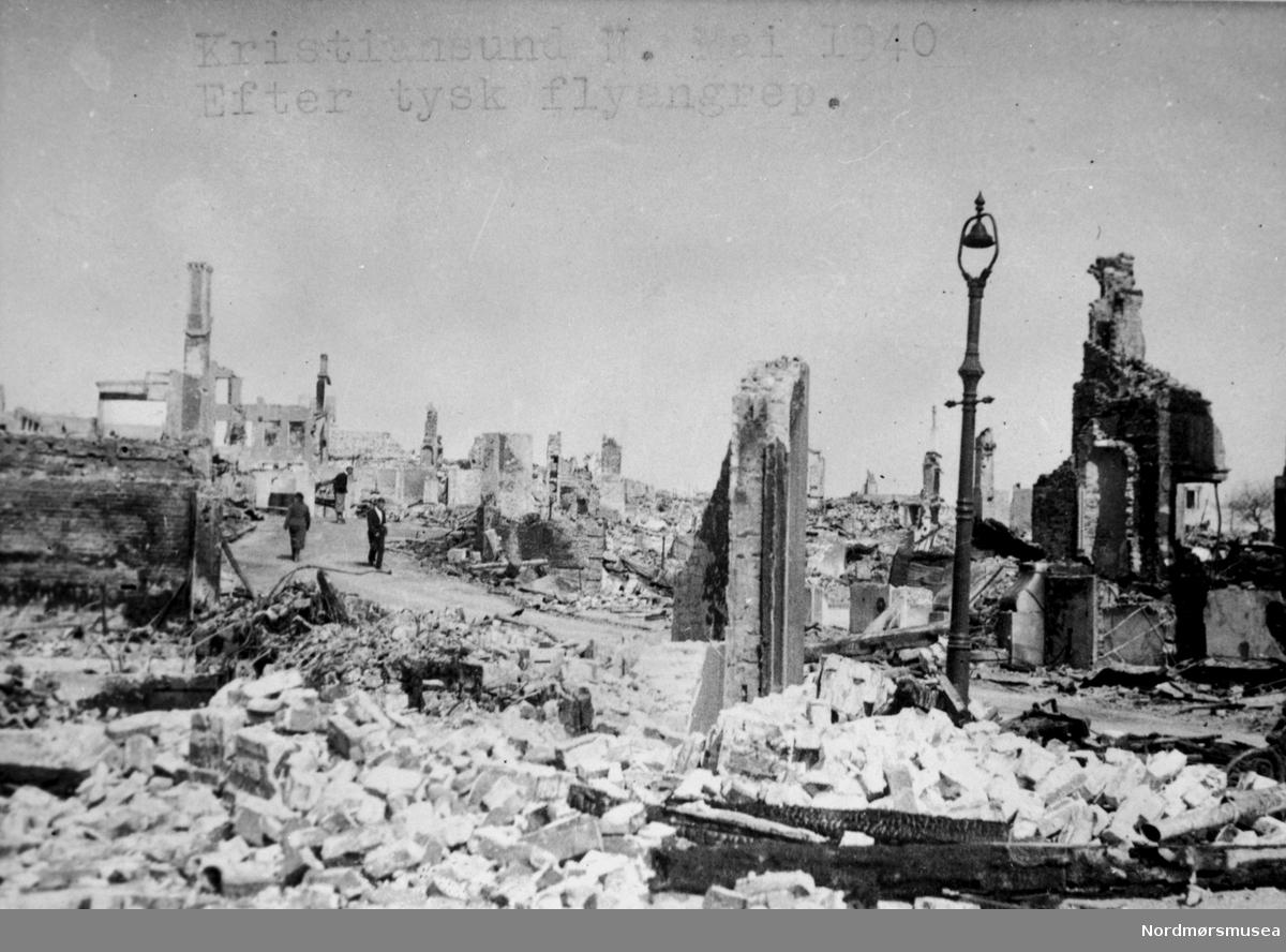 """"""";Kristiansund N. Mai 1940 Efter tysk flyangrep.""""; Krigen har kommet til Kristiansund. Etter nazistenes herjinger i perioden 28. april til 1. mai 1940 ligger store deler av byen i ruiner.  Etter bombigen løp det totale antall brente bygg på tilsammen 767, hvor 605 av disse var på Kirkelandet og 162 på andre """";land""""; i Kristiansund. Her fantes det til blant annet til sammen 3906 boliger ifølge boligtellingen av 1938, og av disse brant 2162 boliger ned og 7099 mennesker ble husløse. I tillegg til de 767 brente byggene brant 36 fiskepakkehus ned til grunnen, hvorav 34 lå på andre """";land"""";. Verdien av de brente byggene beløp seg til kroner 26,9 millioner for Kirkelandet (kroneverdi per 1940) eller tilsammen 30,6 millioner kroner (kroneverdi per 1940) for hele byen. Fra Nordmøre Museums fotosamlinger. Kilde: Gjenreisningsproblemer i Kristiansund. Fremlagt ved gjenreisningsinstituttet i Kristiansund. Juli 1945. Side 16 - 20."""