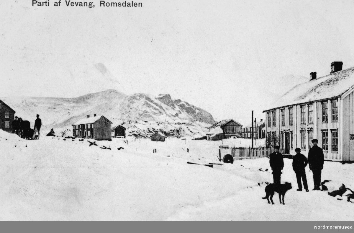 Prospektkort og vinterbilde fra Vevang i Romsdal og Eide kommune, hvor vi ser diverse våninghus og uthus. Her ser vi blant annet to personer med hest og vogn til venstre, mens til høyre ser vi tre gutter med en hund. Ellers så ligger det et postkontor i bygget like bak guttene. Fra Nordmøre Museums fotosamlinger.