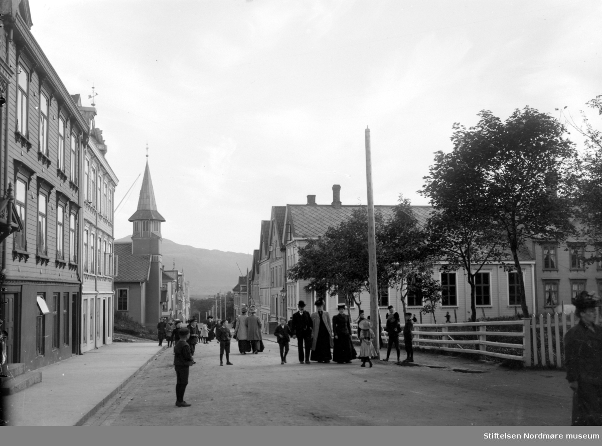 Fra Langveien med Roligheten til høyre. Ellers så ser vi Baptistkirken/ misjonskirken til venstre, med Frelsesarmeen rett over gaten til høyre. Folk  spaserer langs gaten i sine penklær, så bildet er muligens fotografert en søndag. Fra Nordmøre Museums fotosamlinger.