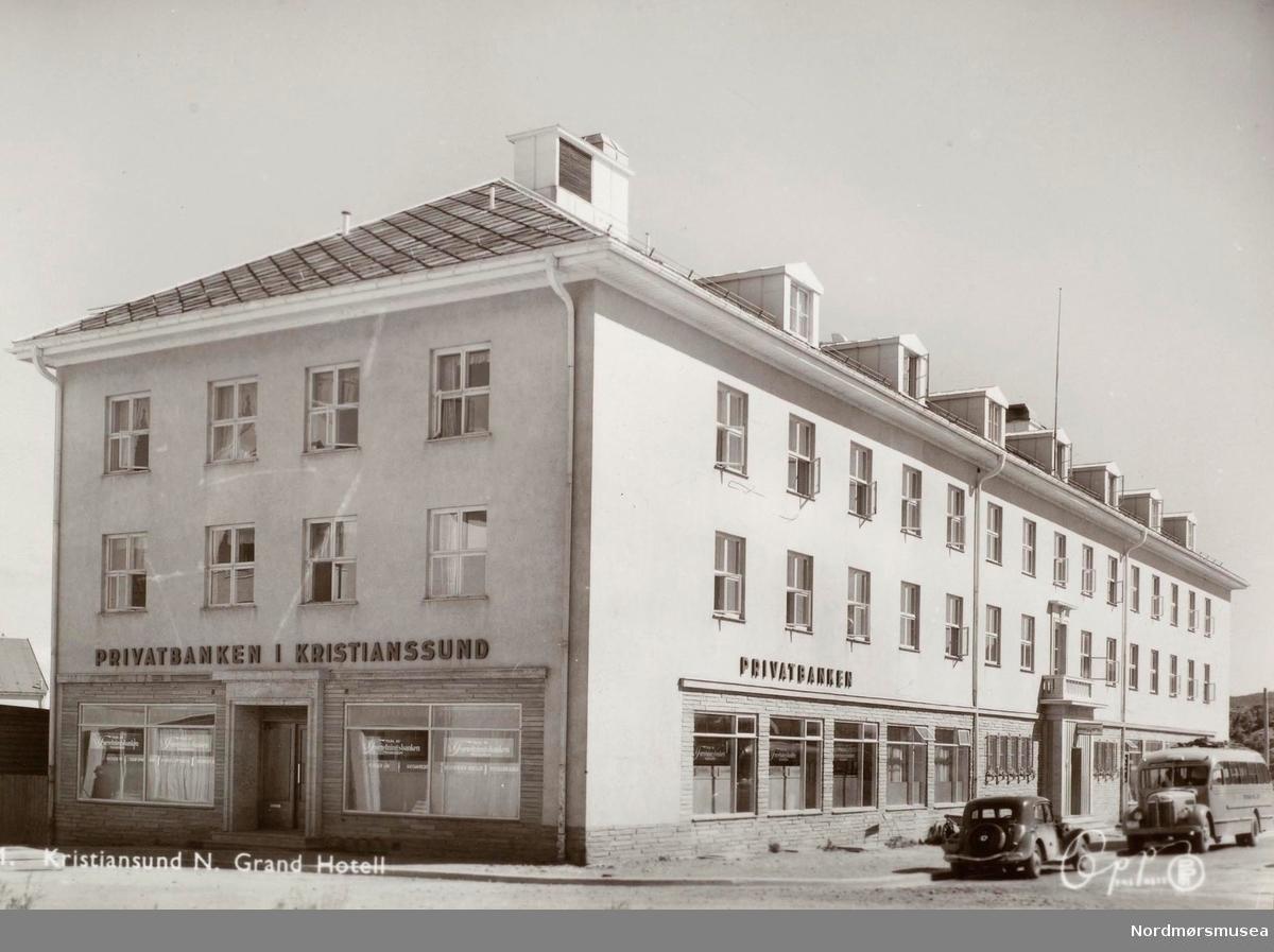 """Postkort """"11"""", med et bilde av byens Grand Hotell med Privatbanken i deler av 1. etasje, på Kirkelandet i Kristiansund.  Bilen er en Citroën og bussen en International årsmodell 1946-48 (info: Ivar E. Stav). Her var avgangsstedet for alle fjernbusser og nullpunktet for avstandsberegning fra Kristiansund by. - Etter at byens andre Grand Hotell ble satt i brann i aprildagene 1940 og tyskerne tok over byen, ble det raskt bestemt at hotellet skulle bygges opp igjen. Dette skyldtes utvilsomt tyskernes prekære behov for et hotell.  Tomten ble ryddet og stod klar i 1941, og i juli samme år døde eieren av Grand Hotell Nils Nilsen. Hans nærmeste arvinger Elise og Esther Nilsen overdro senere i januar 1942 eiendommen Torvet 7 til A/S Grandgården, som da hadde fått godkjent anmeldelse av nybygg.  Mens det første Grand Hotell ble bygd i Sveiterstil og byens andre ble bygd i en nøktern variant av jugendstil, ville det tredje hotellet, som nå ville bli oppført med moderne materialer, bli reist i en kombinasjon av nyklassisisme og funksjonalisme.   Entreprenøren av det tredje Grand Hotell var A/S Vestlandsbygg og byggherre var Konsul Odd Blom Nielsen, innehaver av Jernvarefirmaet Ingwald Nielsen i Oslo, på vegne av A/S Grandgården. Arkitekten bak bygget var Hugo A. Brustad, Oslo  Torsdag 21. mai 1942 stod nybygget klart, og det ble slått stort opp at hotellet ville bli åpnet i løpet av september-oktober. Dette skjedde ikke da flere uforutsette hendelser dukket opp, men 27. februar 1943 slo avisene opp at Grand stod nå i disse dager klart til å taes i bruk. Komplekset ble 58 meter i lengden og 14,5 meter i bredden, og alt i alt fikk hotellet 67 gjesterom.  Flere endringer skjedde i de kommende årene. Restaurantdriften var en av dem. Den 8. mai 1951 ble Palmetten åpnet, etterfulgt senere av etableringen av Gripsalen i den gamle Grandkjelleren. I denne kom det nå inn flotte malerier utført av Einar Granum og Tidens Krav kunne lørdag 19. september 1953 melde om at Vi har fått en Grips"""