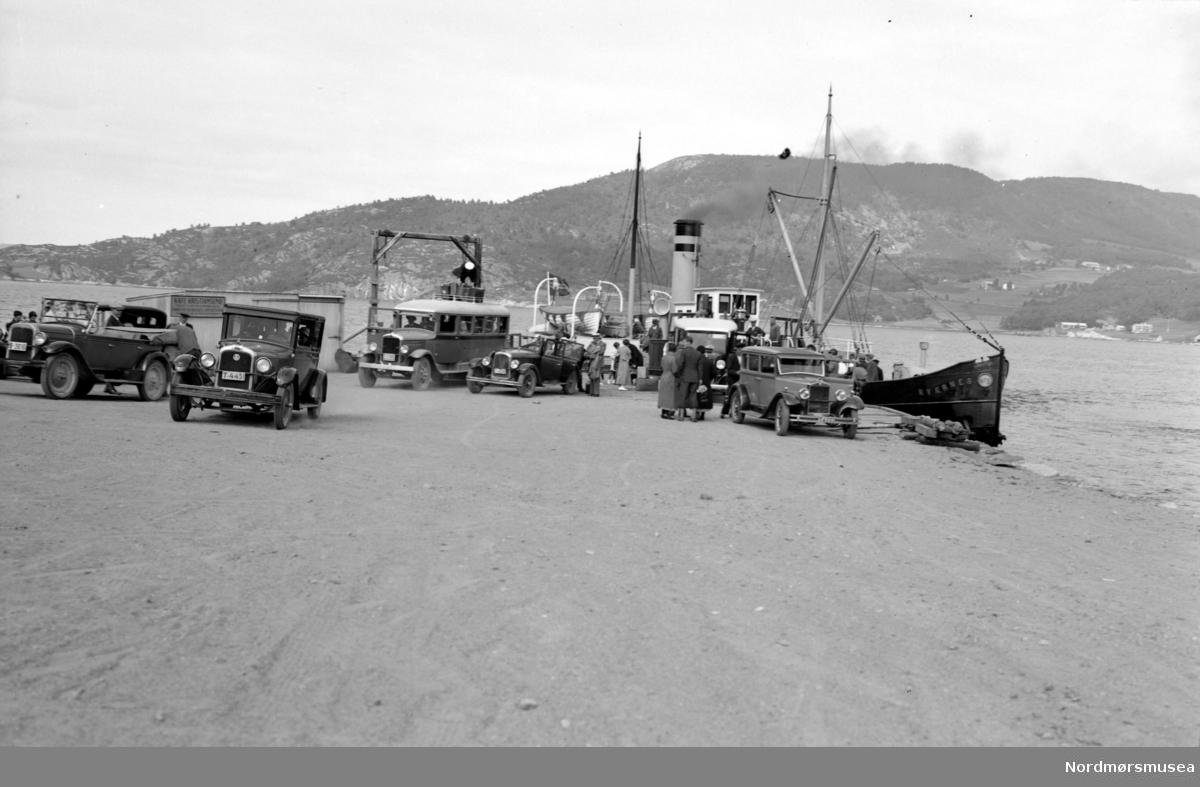"""Rutebåt DS Kvernes ved Gjemnes fergekai. Flere biler og en buss står parkert foran. Bilen til venstre er en Chevrolet 1927, bussen muligens en GMC. (Info: Ivar E. Stav 2016). Fotograf er G. Sverdrup.  Dette bildet kan tidfestes nærmere, til 1932-1938. I 1932 ble veien Batnfjordsøra-Gjemnes åpnet. Gjemnes fikk båtanløp fra Kristiansund, og trafikken til Batnfjordsøra kunne gå med bil eller buss. Noen rutebåter, som D/S Kvernes på bildet, kunne ta med noen få biler. Først i 1938 fikk Gjemnes fast ferjesamband med B/F Trygge som ble satt i rute Kristiansund-Gjemnes-Torvikbukt. Dette bildet er ellers gjengitt og omtalt på side 294 i Ulstein, R. (1995). """"Som skyttel i vev"""" (bind 1). Molde: Møre og Romsdal fylkesbåtar. (Info: Sveinung Berild - 09.11.2016). Fra Nordmøre museums fotosamlinger. Samme bilde som Kmb-1987-005.3953"""