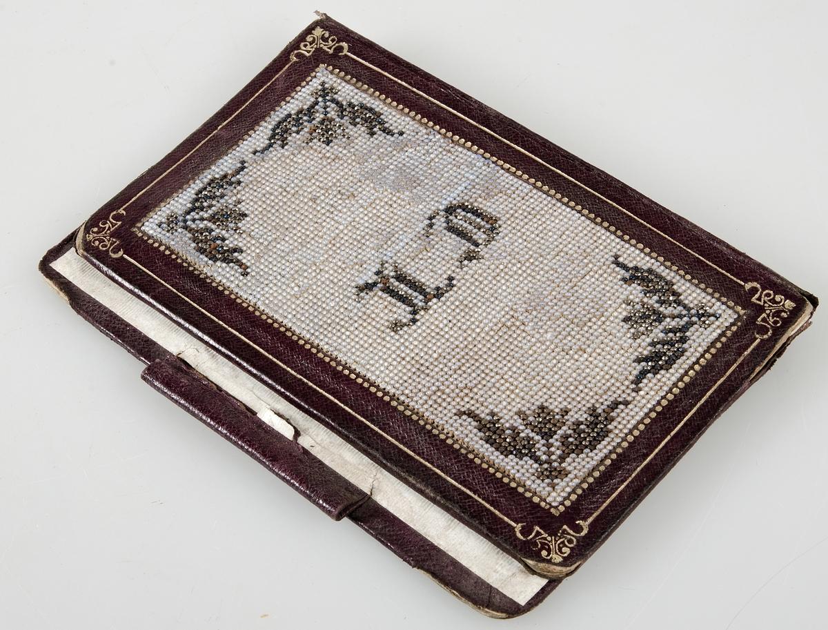 Pärm av mörkrött pressat skinn med guldtryck, på pappstomme. På framsidan pärlbroderi i brunt och svart mot botten av ljusblå pärlor. Bakre pärmen har i kanten hylsa för penna.