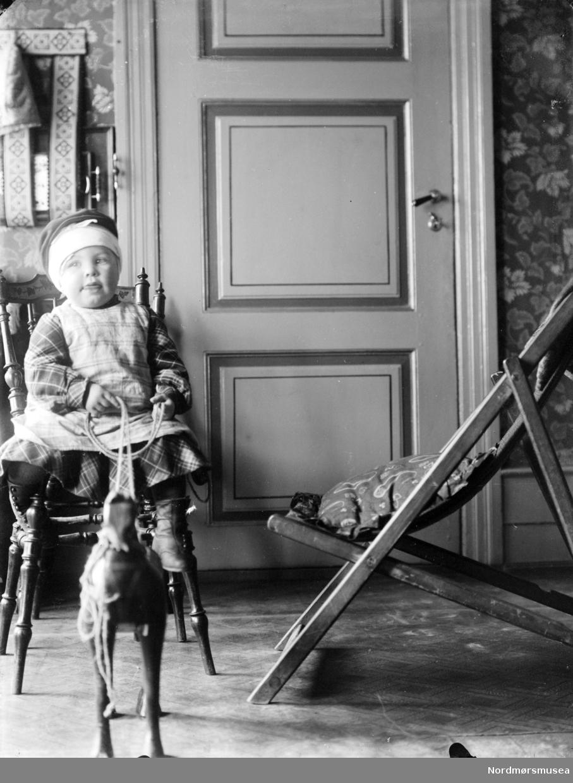 Foto av et barn som leker med en lekehest. Kan være fra Sverdrupfamilien/slekten, eventuelt fra deres bekjentskaper. Datering er ukjent, men trolig omkring 1920 til 1930. Fra Nordmøre museums fotosamlinger. EFR2015