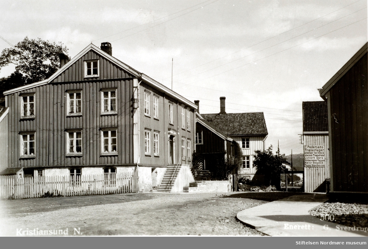"""Postkortet har inskripsjonen """";Kristiansund N""""; og er stemplet """";Eneret G. Sverdrup""""; ved Sverdrups Bokhandel som utgiver. Georg Sverdrup var trolig både fotograf og utgiver av postkortet Denne gården overlevde bombingen av Kristiansund i aprildagene 1940, men måtte rives etter krigen for å skaffe plass til Rutebilstasjonen. Til høyre ser vi at Torstein Pedersen annonserer for trelastvarer. Før 1940 var dette området tett bebygd med boliger, håndverkere og brygger. Ifølge Berhard Jordfald som skriver i """"FRA VÅGABAKKEN TIL ØVREVÅGEN Trekk fra bydelen Vågen i Kristiansund i 1860-70 årene"""" at """" i Holmagaten 3, nå (1940 før bombingen av byen) Karl Sylthes, tidligere M. H. Astrups gård, bodde den gang marinekaptein C. F. Rode. Han var navigasjonslærer og bestyrer av styrmannsskolen her i byen, som også hadde sine lokaler der. Kaptein Rode hadde 2 sønner, Carl og William, og en datter. Denne ene av sønnene, Carl Rode, lever og har vært ingeniør i fyrvesenet. Styrmannsskolens lokaler i Vågen benyttedes også, i vintermånedene, av en offentlig tegneskole som aftenskole, spesielt for ungdom i forskjellige håndverksfag. Dekorasjonsmaler Wilberg var lærer i frihåndstegning og ingeniør-kaptein og stadsingeniør Bødtker i konstruksjonstegning. Blant de mange hånderkslærlinger, som i 1870-årene om vinterkveldene, i tiden fra kl. 7 til 9 gikk på denne tegneskolen, ble flere senere fremragende håndverker og utmerkede samfunnsborgere"""". (Fra Nordmøre Museums fotosamlinger.)"""