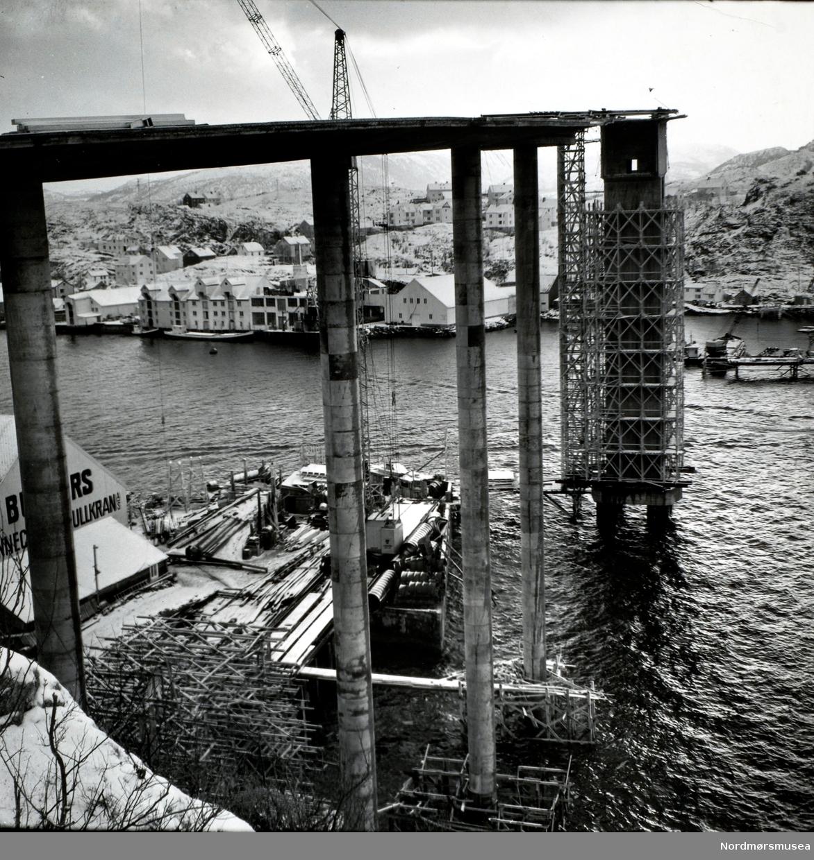 Foto fra byggingen av Sørsundbroen. Broen vil bli omkring 408 meter lang og 9,3 meter bred, med en fri høyde over vannet på omkring 39,6 meter. Broen vil veie bort i mot 10.000 tonn når den er ferdigbygd. Det er circa 50 meter mellom pilarene med 100 meter på det meste midt på, samt beregnet til et akseltrykk på 10 tonn. Broen stod ferdig omkring sommeren 1963. Entreprenør var Vestlandsbygg A/S, og arbeidet ledes av firmaets sjef (per 17.02.62), sivilingeniør H. Nafstad. Kilde: Avis. Nordmørsposten eller Romsdalsposten? Lørdag 17. februar 1962. Fra Nordmøre museums fotosamlinger.
