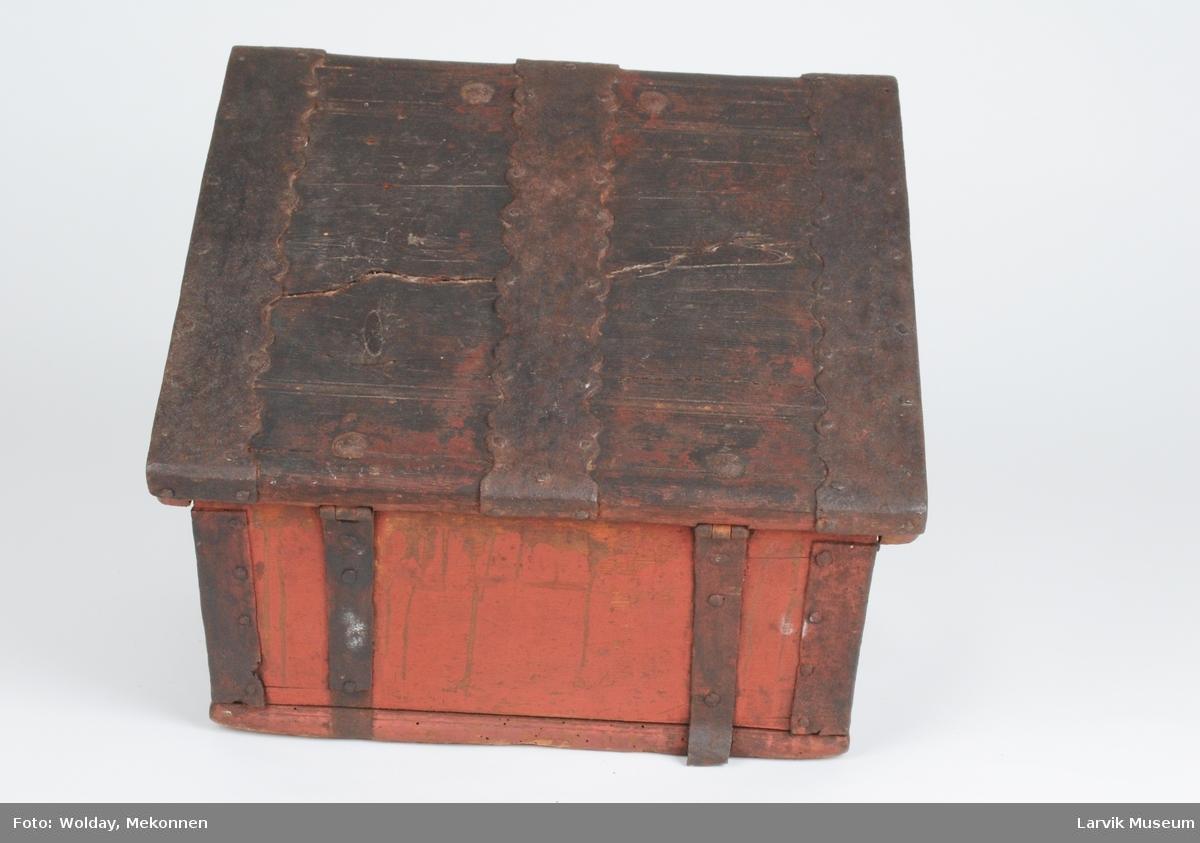 Form: rekt.gr.fl., skrå rygg. rett lokk med lister på sidene. jernbeslag på hjørner, innside og utside av lokket samt nøkkelhull. c-formet jernhåndtak på sidene, to bøyler for låseklakk på lokket.