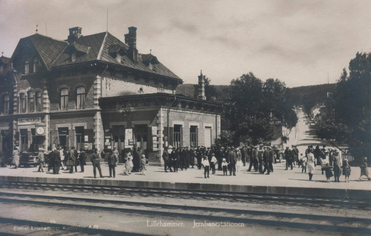 Lillehammer stasjon på Eidsvoll-Dombåsbanen. Mange pyntede mennesker er møtt frem på plattformen.