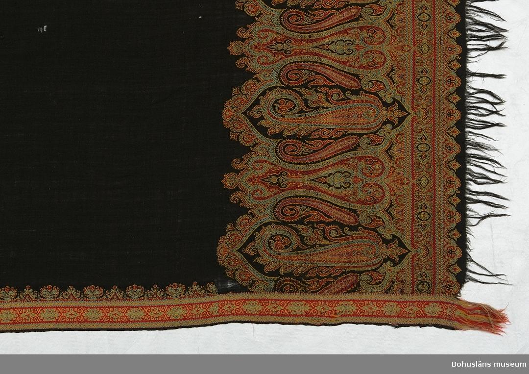 """Rektangulär schal med svart bottenfärg och bårder med ett detaljerat orientalisk-inspirerat mönster i rött, gult och ljusblått. Smal småmönstrad bård på mitten markerar var schalen skulle vikas. Liknande smala bårder finns även längs lång- och kortsidorna. Vid kortsidorna innanför den smala bården en bred bård av medaljonger med mir-i-botha-motiv (även kallat """"schalgurka"""", flamman med mera, se litteraturlistan Sandberg). Paisleyschalar, som schalar av denna typ kallas även om de inte alltid är gjorda i Paisley (Skottland), har ofta mir-i-botha-motiv. Därför har det med tiden även kommit att kallas """"paisley-mönster"""". På grund av det komplicerade mönstret kan man med säkerhet säga att schalen är vävd i vävstol med jacquardmaskin. Schalar av det här formatet började vävas på 1840-talet i samband med att krinolinen kom. Schalar av Paisleytyp miste sin populäritet på 1870-talet, sista schalen vävdes i Paisley 1886. Dateringen gjord utifrån de uppgifterna.  Schalen var en gåva från givarens far till hans mor. Modern hette Julia Mattiasson, född 1876 i Nolby, Solberga socken. Enligt gåvans förmedlare hade hon ej råd att använda den för att det var för fint. Ytterligare personuppgifter se UM026244. Textilierna UM026244 - UM026246 har mestadels förvarats i en """"uppbäddad säng"""" i hemmet i Nolby. Schalen är av okänt ursprung. Stort hål vid mittbården. Ett stort och flera mindre hål i svarta partierna. Ett hål i breda bården vid ena kortsidan. Bristningar. Fransarna slitna. Blekt. Ljusbruna fläckar här och var."""