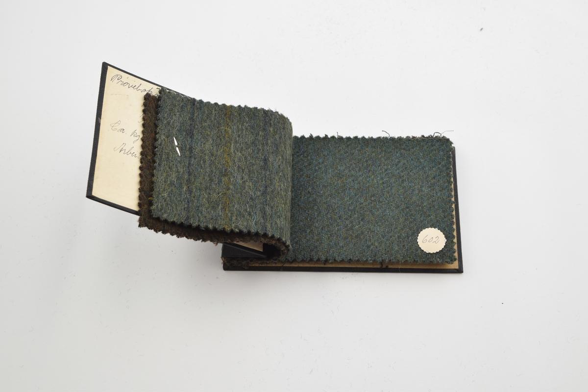 Prøvebok med 6 prøver. Tykke ullstoff med striper eller uten utpreget mønster. Alle stoffer er merket med en rund papirlapp festet med melallstifter hvor nummer er påskrevet for hånd. Stoffene er i mørke grønne og brune farger.  Stoff nr. 606 (grønn/sort stripet), 604 (grønn/sort), 602 (grønn), 601 (mørk grønn), 600 (mørk grønn), 599 (brun-grønn).
