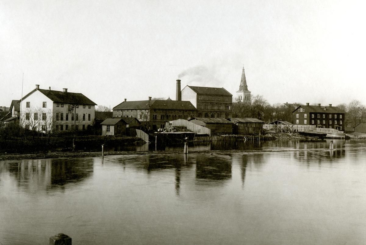 """Vy över Wennergrenska garveriet, guldlistfabriken och """"trevåninga"""" längs älven mellan Östra bron och pråmkanalen. Bilden tagen ca år 1900."""