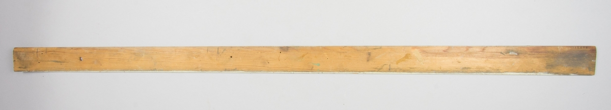 Linjal av lövträ med vertikala blyertslinjer samt blyertskryss. Längs ovansidan rester av gulvit färg. Hål för upphängning samt fem mindre hål.
