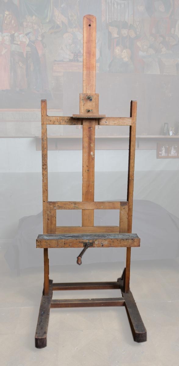 Staffli av ek med två sidostycken/ben som avslutas med vinkelställd fot, med hjul. Benen fixerade med metallstag i foten. Mittpartiet höj- och sänkbart med vev. Hylla som stöd för målningen som låses upptill med träkloss med muttrar. Vev.