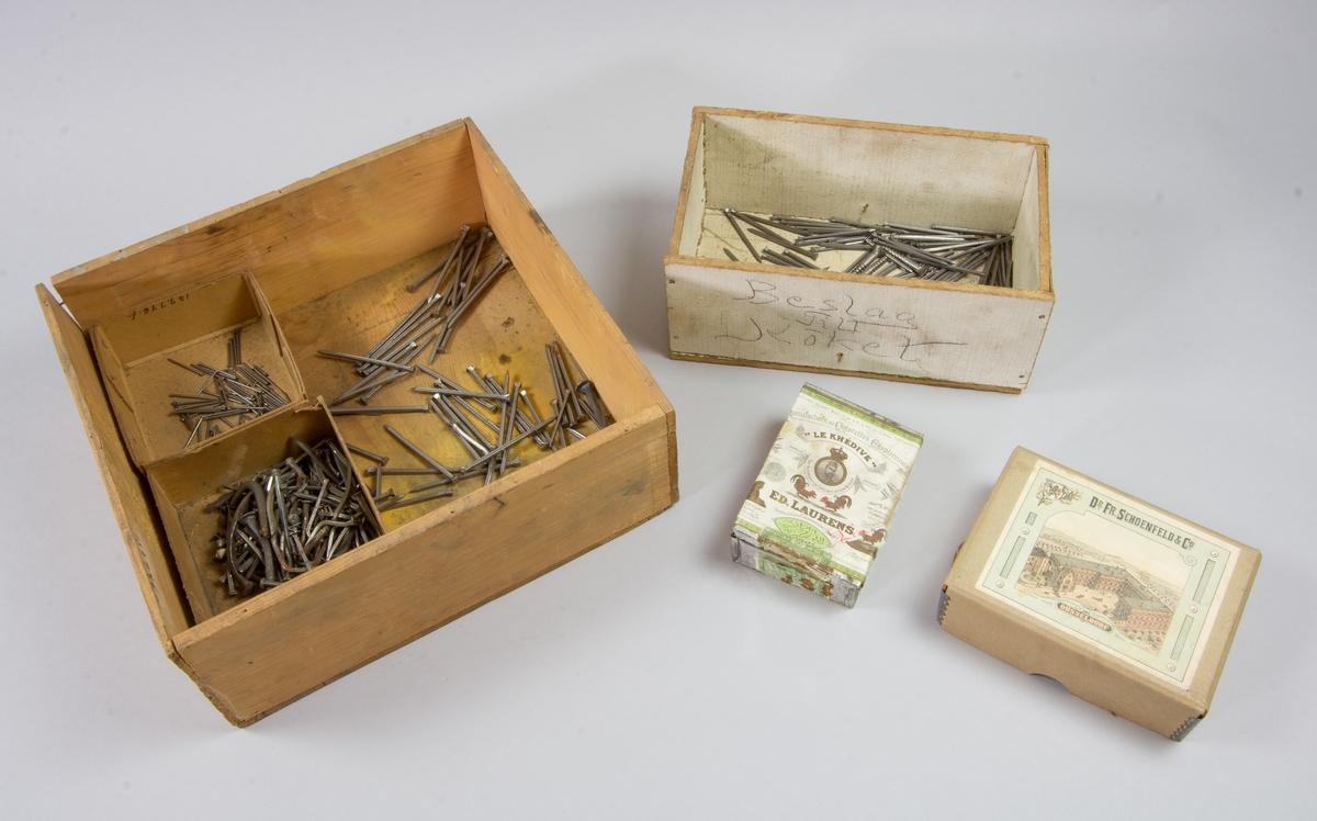 Spiklåda av trä, utan lock innehållande spik. I spiklådan två mindre pappaskar innehållande spik, delvis använd. Ytterligare trälåda, vitmålad, innehållande spik och tre skruvar. I lådan ligger ask av brun papp förstärkt med metallbeslag i hörnen för konstnärsfärg. Utan innehåll. I lådan ligger även en plåtask med lock och påklistrad pappersetikett med fabriksmärke för tobak. Innehåller ett fåtal nubb.