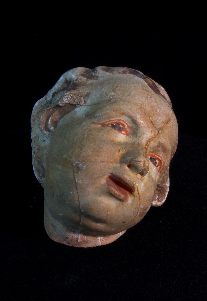 Studiemodell av gips föreställande barnhuvud. Delvis färglagd.