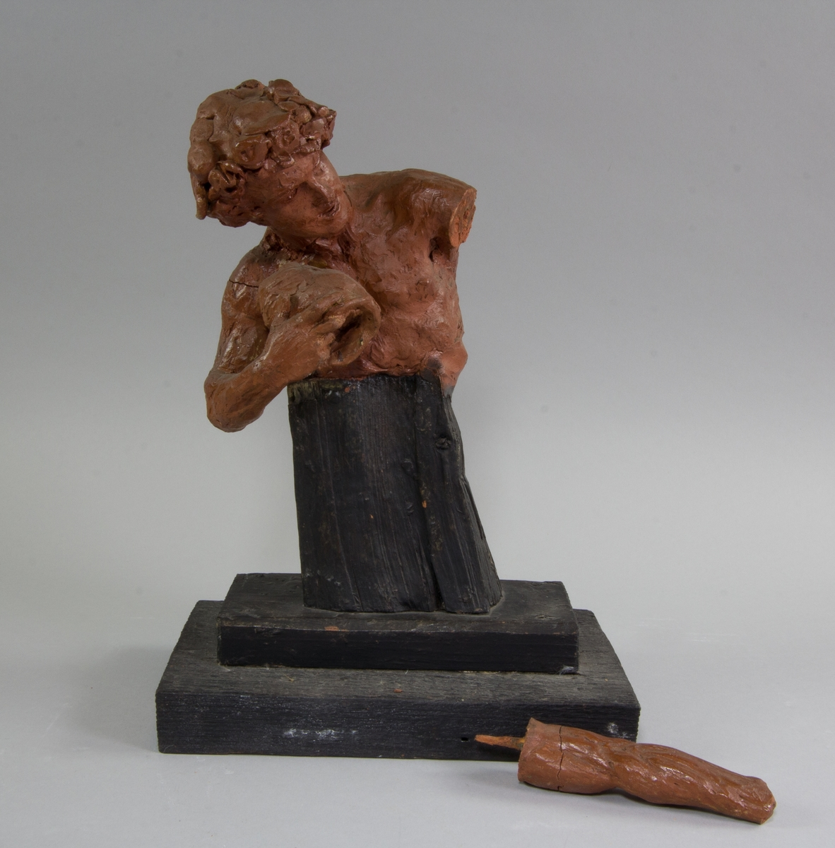 Triton, bröstbild, med blomsterkrans i håret. Håller en snäcka i ena handen och den andra armen utsträckt.