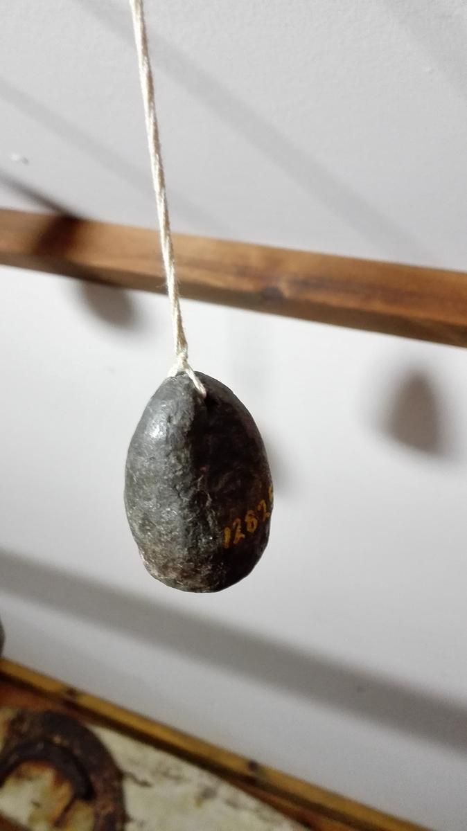 """2 sildelodd (12824 - 25)  To sildelodd av bly for sökning efter brisling. Konf. nr. 11864 - 66, hvor bruken er beskrevet. Begge lodd er hamret av bly, det ene meget större end det andet.  Samtlige forannevnte gjenstander (12815 - 12842) fandtes i den gamle """"Bondestue"""" paa Glavær, hvilken er indkjöpt med inventar til samlingerne. Josefine Mehus paastod imidlertid, at hun eiet endel av gjenstandene, bl.a. 12815, 12816, 12817, 12819, 12820, 12827, 12828, 12829, 12832 og 12842. Da eiendomsretten var uviss, avfandt jeg mig med hende mot et vederlag av kr. 25.  Kjöpt av Josefine Mehus, Glavær."""