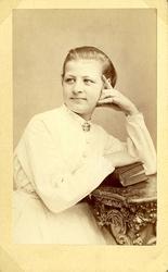 Porträtt (midjebild, halvprofil) av en ung kvinna i ljus, pr
