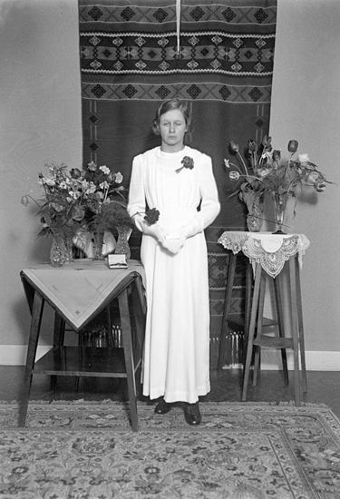 Foto av en okänd kvinnlig konfirmand i lång vit konfirmationsklänning.